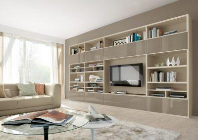 Libreria soggiorno con vano porta tv che accosta le finiture laccato lucido ed effetto legno.
