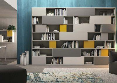 Parete libreria che alterna vani a giorno ad ante liberamente alternabili e componibili.