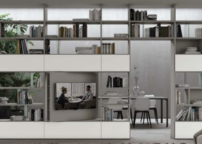Parete libreria bifacciale che permette di separare gli ambienti fungendo da soggiorno, libreria, porta tv, divisorio.