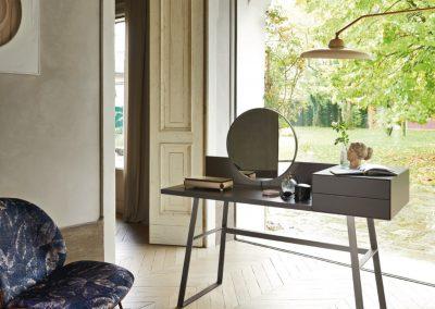 Scrivania dalle linee essenziali e minimaliste, con gambe in metallo verniciato, cassetti e specchio.