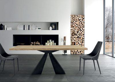 Tavolo fisso o allungabile disponibile con piano scortecciato, vetro o marmo e sedia imbottita in pelle.