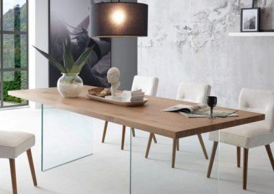 Tavolo fisso o allungabile con piano scortecciato e gambe in vetro.