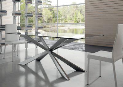 Tavolo fisso con piano vetro o piano scortecciato in legno con basamento laccato.